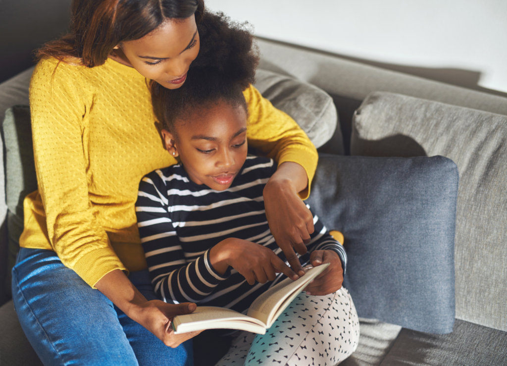Black mom learning daughter to read sitting at home in sofa smiling