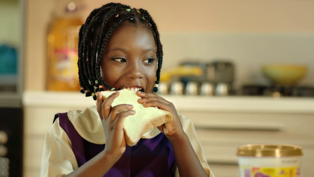 image of a little black girl eating Mamador butter and bread. Healthy Breakfast